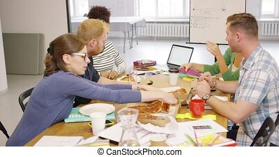 Colleagues eating pizza during break - Group of colleagues...