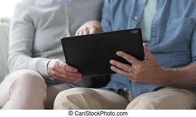 senior couple with tablet pc at home - family, technology,...