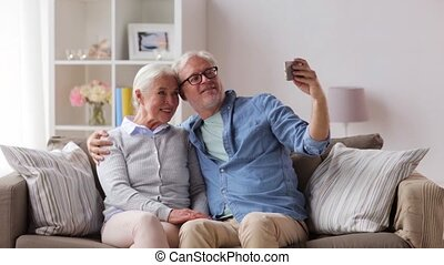 happy senior couple with smartphone at home - family,...