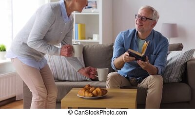 happy senior couple drinking coffee at home - family,...
