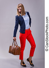 Fashion look of woman dressed red pants, blue jacket, brown...