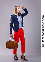girl in red pants with a leather bag looking into the...