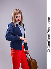 girl in red pants and with leather bag looking at watch over...