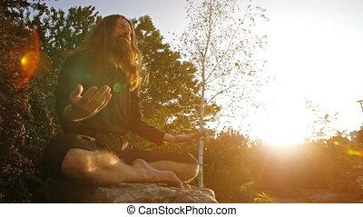 Yogi Meditating on sunset - Yogi sitting in meditation on...