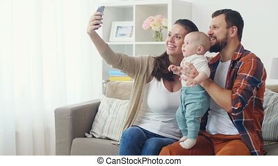 mother and father with baby taking selfie at home - family,...