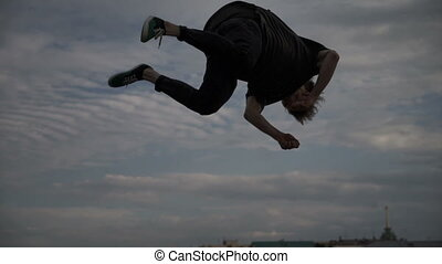 Silhouette of a guy doing a somersault in the street