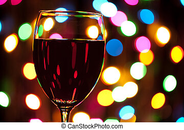 Nightlife - Wine glass with defocused color lights in the...