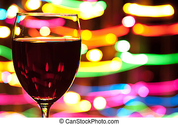 Glass of wine with blured motion lights in the background