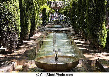 View of water fountain and trees at Hort del Rei park next...