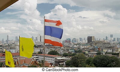 Thailand state flag fluttering in the wind on the top of Wat...