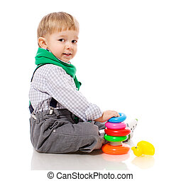 Toddler boy playing with colorful pyramid toy isolated on...