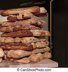 Heap of Bread Rolls Assortment and French Loaf on Wooden...