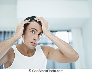 male beauty - caucasian adult man checking hairline....
