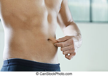 male beauty - cropped view of young caucasian man measuring...