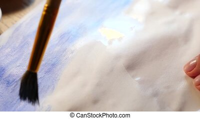the artist paints paints on a white sheet. close-up of a...