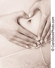 Female hands forming heart shape on belly. - Body care and...