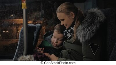 Mom and kid playing on mobile during evening bus ride -...