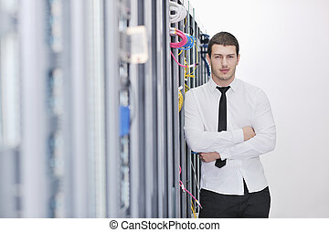 young engeneer in datacenter server room