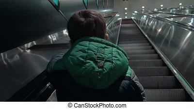 Boy moving up on escalator in subway - Back view of a child...