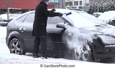man clean car snowy window with brush in winter time. 4K -...
