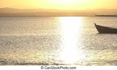 Sunset over lake with tourist boat backlit - Long shot of...