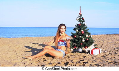 girl on the beach under the Christmas tree for Christmas in...