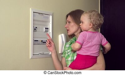 woman with baby in arm check circuit breaker electrical...