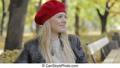 Woman in red beret sitting on bench - Attractive woman in...
