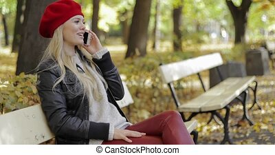 Woman in red beret speaking on phone - Beautiful woman in...