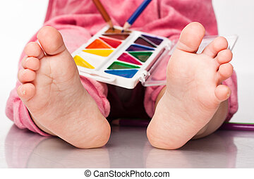 Babys feet with paint and pencils isolated on white