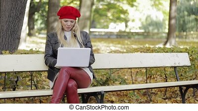 Smiling woman using laptop in park