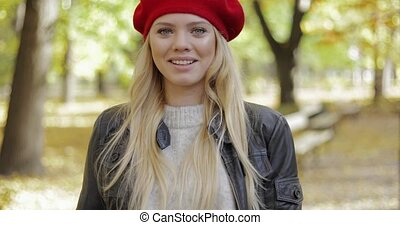 Woman in red beret walking in park - Attractive young woman...