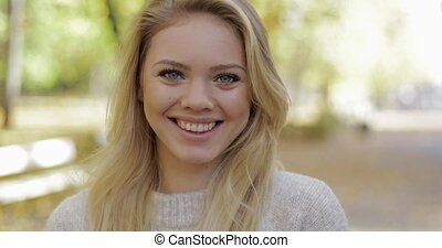 Attractive woman in park - Attractive woman with cute smile...