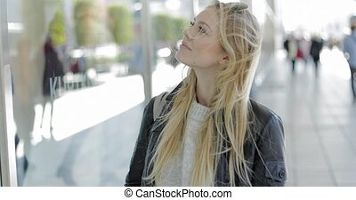Pretty woman looking at shop-window - Pretty young woman in...