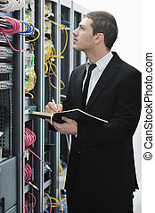 businessman withnotebook in network server room - young...