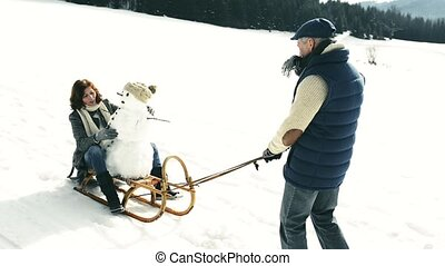 Senior couple pulling a snowman on a sledge in winter...