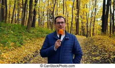 Middle-aged man tv correspondent leads a report with a...