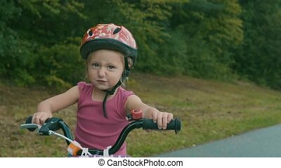 Little girl is cycling in the nature. - Close up of cute...