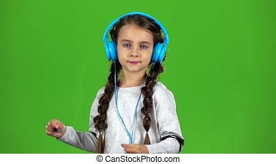 Baby in the headphones is listening to music. Green screen....