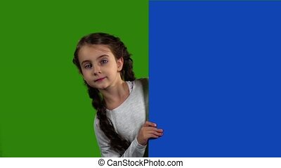 Baby looks out from behind an empty board. Green screen....