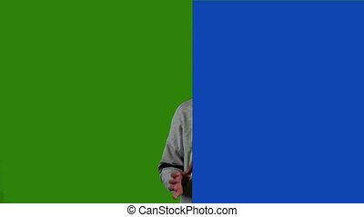 Child looks out from behind the blue board and laughs. Green...