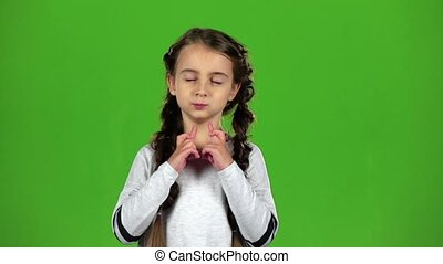 Child crosses his fingers in his arms. Green screen. Slow...