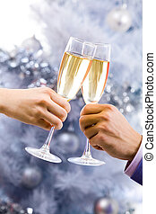 Cheers - Close-up of champagne flutes in human hands during...