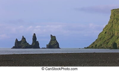 The basalt sea stacks Reynisdrangar situated under the...