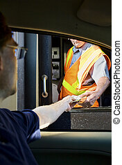 Man paying moneyl at toll booth - Man paying money at toll...