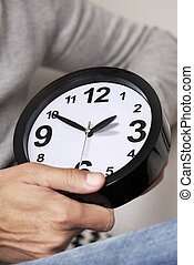 man adjusting the time of a clock - closeup of a young...
