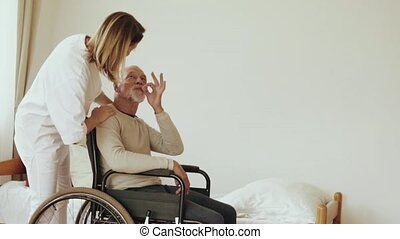 Health visitor and a senior man during home visit. A nurse...