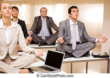 Relaxation time - Portrait of meditating business people...