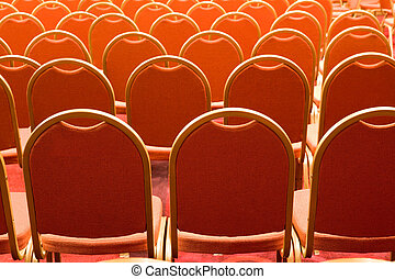 Conference hall - Image of several rows of red armchairs in...