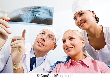 At the dentists - Image of young lady with dentist and nurse...